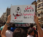Demonstrators raise a banner demanding that ISIS (DAESH in Arabic) leaves Syria