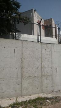 Mauern und Stacheldraht am ehemaligen Wohnheim-Gebäude (Friedensratschlag Hatay)