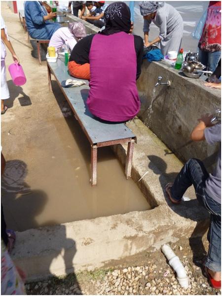 Frauen spülen Geschirr unter freiem Himmel im Lager YİBO in Yayladağı (2. Bericht des Friedensratschlags Hatay - April 2016)