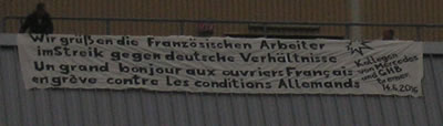 """Vom Dach der Halle 7 des Bremer Mercedes-Werkes hängt ein Großtransparent mit folgendem Gruß von Mercedes-Arbeitern an die französischen Arbeiter, anlässlich ihres Großkampftages am heutigen Tag: """"WIR GRÜSSEN DIE FRANZÖSICHEN ARBEITER IM STREIK GEGEN DEUTSCHE VERHÄLTNISSE"""