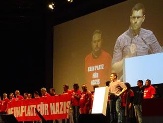 """T-Shirts mit der Aufschrift """"Kein Platz für NAZIS"""" - Aktion auf der Betriebsversammlung bei Daimler in Untertürkheim am 22.3.2018"""