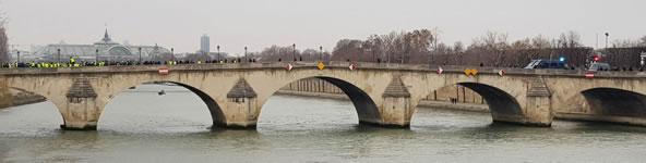 """Foto von Bernard Schmid: Stilleben mit """"Gelbwesten"""" (links) und blauen Einsatzkräften (rechts) über der Seine (Demo in Paris am 5.1.19)"""