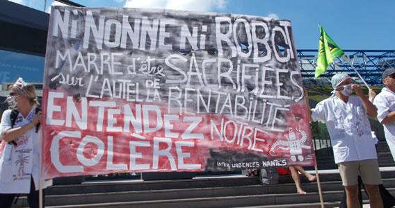 """Foto von Bernd Landsiedel vom 2.7.2019 in Paris: Transparent Beschäftigter der Notaufnahmen: """"Weder Nonnen noch Roboter. Wir haben es satt, auf dem Altar der Rentabilität geopfert zu werden. Hört unsere Wut"""""""