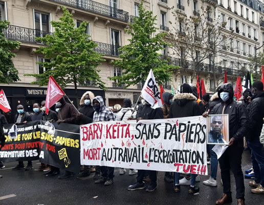 """Foto von Bernard Schmid der Pariser Demo am 1.5.2021: Transparent zum Tod eines migrantischen Arbeiters (""""Sans papiers""""), der vorige Woche Opfer eines tödlichen Arbeitsunfalls wurde"""